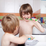 Boy Brushing Teeth While Looking At Brother In Bathroom Royalty Free Stock Image
