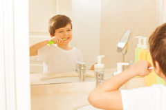 Boy brushing teeth and looking at mirror in bath Royalty Free Stock Image