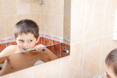 Boy brushing teeth reflection Stock Images
