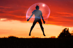 Boy in a Bubble Jumping in the Air Against Sunset Stock Image