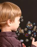 Boy With Bubbles. Young boy wearing striped shirt with bubbles Royalty Free Stock Photography