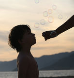 Boy with bubbles. Boy playing with bubbles on the beach at sunset Stock Images
