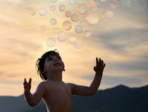 Boy with bubbles. Little boy trying to catch some soap bubbles Royalty Free Stock Images