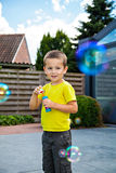 The boy and the bubbles. Cute kid blowing soap bubbles Royalty Free Stock Photography