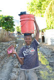 Boy with Bucket. September 26, 2008 - A boy walks through the streets of Gonaives, Haiti after Hurricane Ikedumped tons of mud into the city Royalty Free Stock Images