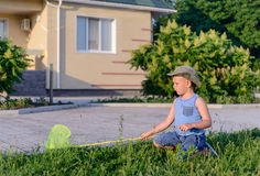 Boy with Bug Net Crouching in Long Grass on Lawn Royalty Free Stock Photography