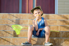 Boy with Bug Net Eating Ice Cream on Steps of Home Stock Photos