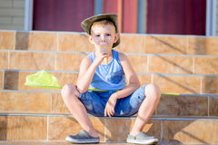 Boy with Bug Net Eating Ice Cream on Steps of Home Royalty Free Stock Photos