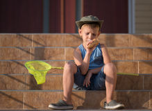 Boy with Bug Net Eating Ice Cream on Steps of Home Royalty Free Stock Photo