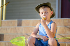 Boy with Bug Net Sitting on Steps Eating Ice Cream Stock Images