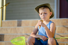 Boy with Bug Net Sitting on Steps Eating Ice Cream Stock Photo