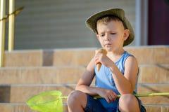 Boy with Bug Net Sitting on Steps Eating Ice Cream Stock Photo