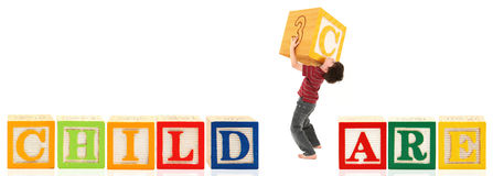 Boy Building Child Care. Adorable seven year old boy building the workd child care with giant blocks Royalty Free Stock Image