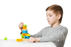 Boy building house made of wooden blocks Stock Image