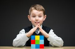 Boy building house from multicolored bricks Stock Images