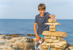 Boy Building Inukshuk Stock Photography