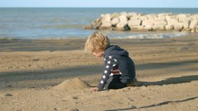 The boy is building a mountain of sand on the beach. stock video footage
