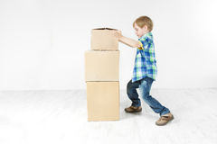 Boy building pyramid of carton boxes. Growth Stock Image