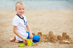 Boy building sand castle on beach Stock Photo