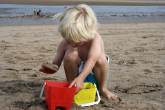 Boy Building Sand Castles. Blonde haired boy playing on the sand on skegness beach Royalty Free Stock Images