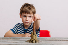 Boy building stack of cash Stock Photography
