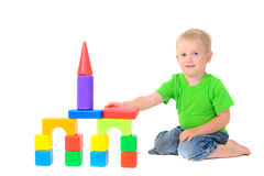 Boy builds a building of colored cubes Stock Photo