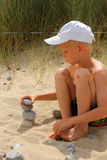 The boy builds the pebbles stack. On the sand Stock Photo