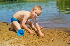 Boy builds a sand stock photo