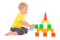Boy builds toy building of colored cubes Stock Images