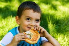 Little boy eating a bun on nature Royalty Free Stock Images