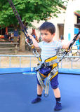 Boy on the bungee trempoline. Little asian boy feeling scared and ready for a bungee trampoline ride Stock Photography