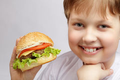 Boy with burger. Happy boy with burger on grey background Royalty Free Stock Photos