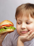 Boy with burger. Happy boy with burger on grey background Royalty Free Stock Image