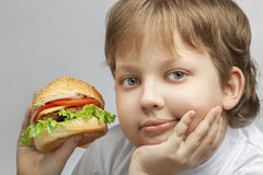 Boy with burger Stock Photos