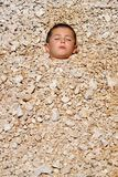 Boy buried in the pebbles Stock Image