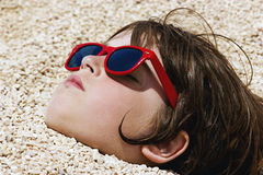 Boy buried in the pebbles on the beach royalty free stock images