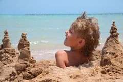 Boy buried in sand royalty free stock photography