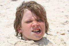 Boy buried in the sand. Boyp buried in the sand at the beach Royalty Free Stock Photos