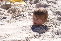 Boy Buried in Sand Stock Images