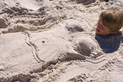 Boy Buried in Sand with Mermaid Body Stock Images