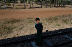 A boy in Burma looks towards a train from the shadows Royalty Free Stock Photography