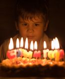 Boy and burning candles. The boy looks at burning candles and is going to blow into them Royalty Free Stock Photo