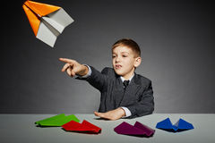 Boy in business suit launching color paper plane Royalty Free Stock Image