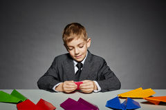 Boy in business suit making color paper planes Royalty Free Stock Images