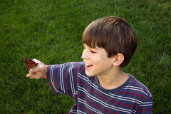 Boy with Butterfly. Boy smiling holding butterfly on finger Stock Photography