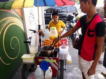 A boy buys kwek-kwek a local delicacy from a street food vendor in Antipolo Royalty Free Stock Images