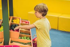 A boy buys toy vegetables in a toy supermarket royalty free stock photography