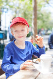 Boy in cafe. Positive smiling boy enjoying desserts and hot cocoa in outdoor cafe, city lifestyle Stock Images