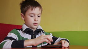 Boy in a cafe with smartphone. Boy in the cafe playing with a smartphone and sends an SMS to a friend stock footage