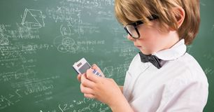 Boy with calculator against green chalkboard with math doodles Stock Photography